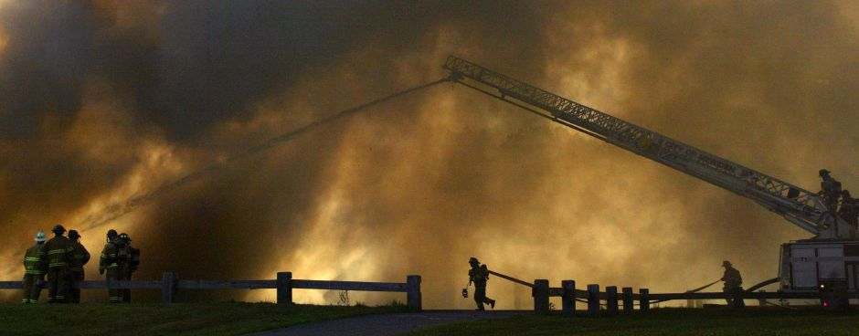 Heavy smoke blocks out afternoon sun as Meriden firefighters work to contain a blaze that consumed insulation tiles next to Thomas Hooker Elementary School on Overlook Rd. in Meriden Sunday August 7, 2005. Two 14-year-old males are in police custody after they allegedly used matches to light a plastic bag on fire in the school