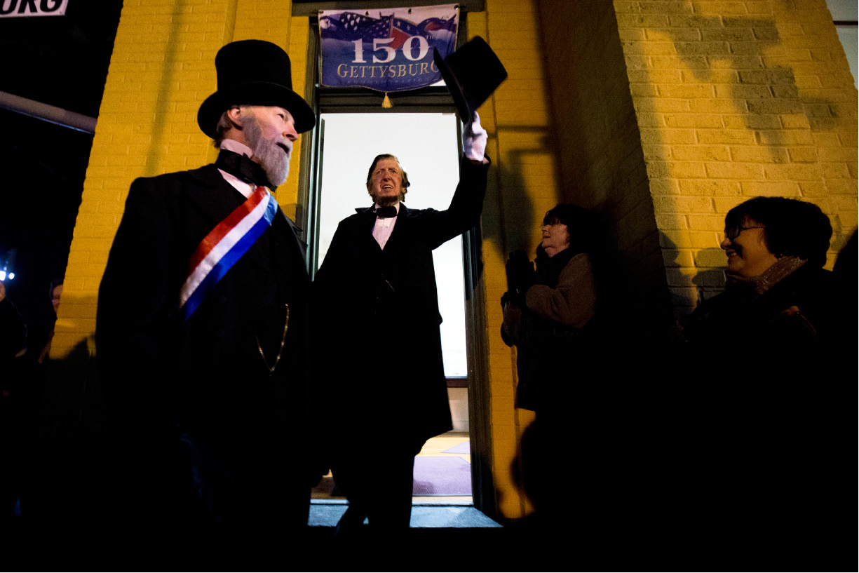 President Abraham Lincoln, portrayed by presenter Robert Costello, center, accompanied by David Wills, who is portrayed by presenter Joe Mieczkowski, tips his hat Monday, Nov. 18, 2013, at the Gettysburg Train Station in Gettysburg, Pa. Tuesday, Nov. 19, marks the 150th anniversary of Lincoln