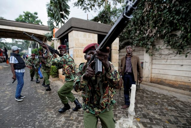 Kenyan security forces aim their weapons up at buildings as they run through a hotel complex in Nairobi, Kenya Tuesday, Jan. 15, 2019. Terrorists attacked an upscale hotel complex in Kenya