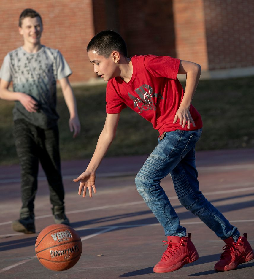 Brian Vives, 12, of Meriden, right, dribbles next to friend, Nathan Murphy, 13, of Berlin, while playing basketball on an unusually warm winter afternoon at Ceppa Field in Meriden, Tues. Feb. 5, 2019. Dave Zajac, Record-Journal
