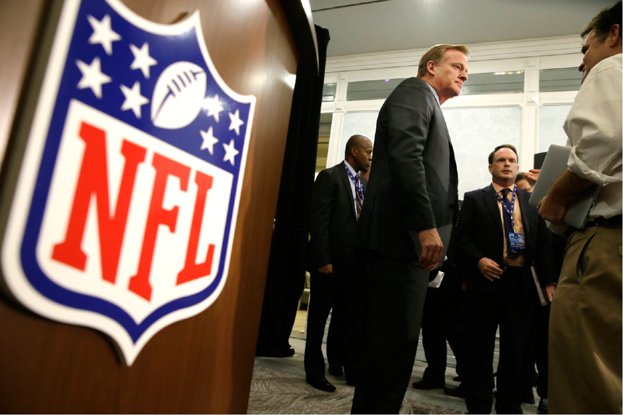Commissioner Roger Goodell listens to a reporter
