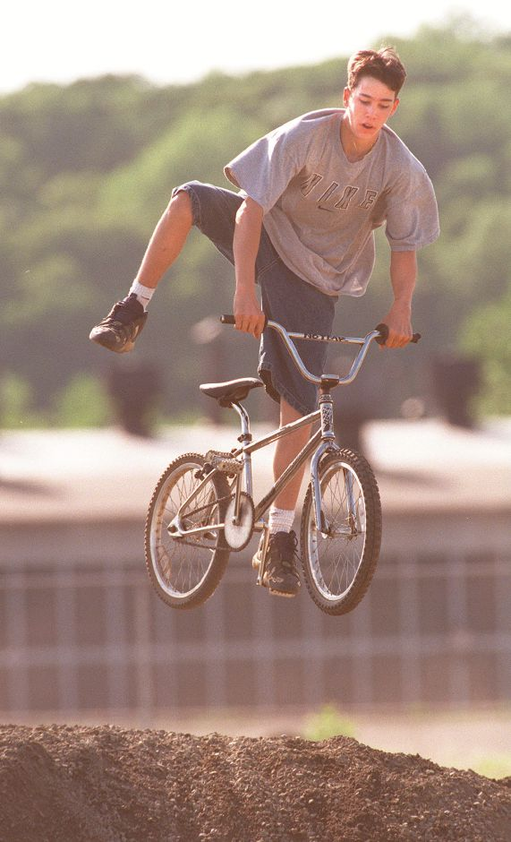 RJ file photo - Dennis Dougan, 16, a student at Sheehan High School, uses a pile of gravel off East Street for bicycle acrobatics after school, May 1998.