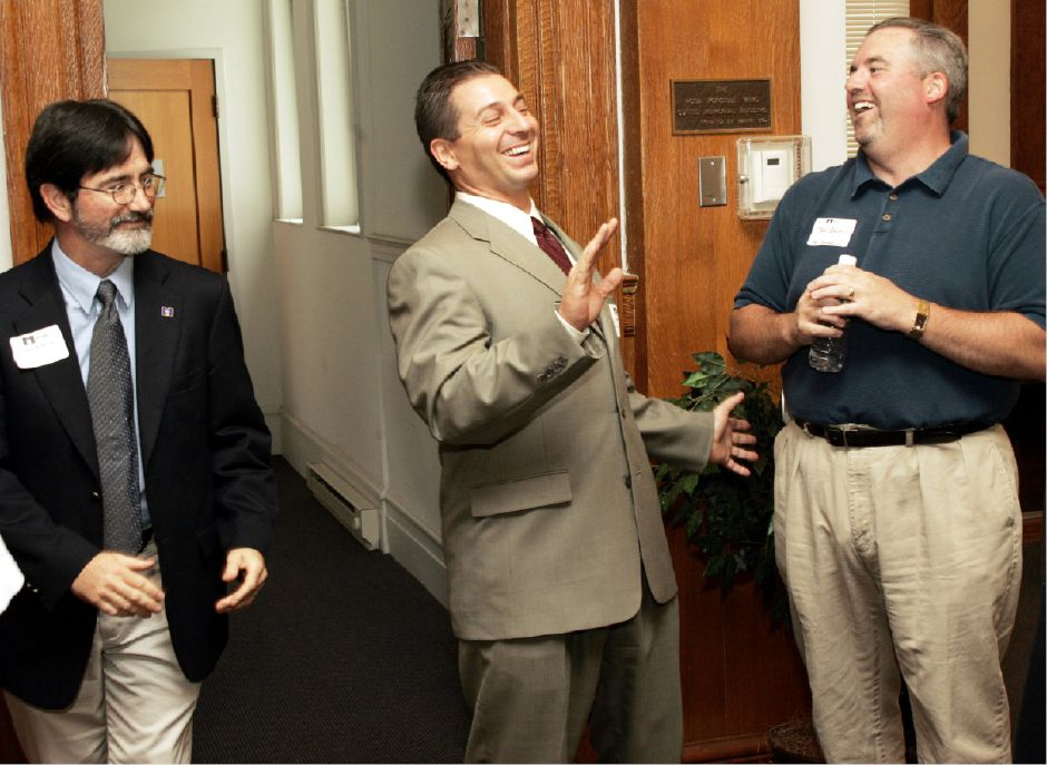 Sean Moore, left, president of the Meriden Chamber of Commerce, with Mayor Mark Benigni, center, and Bob Burns, right, during a light moment at Pizza, Pasta, and Politics at the Curtis Cultural Center Mon. night, June 27, 2005.