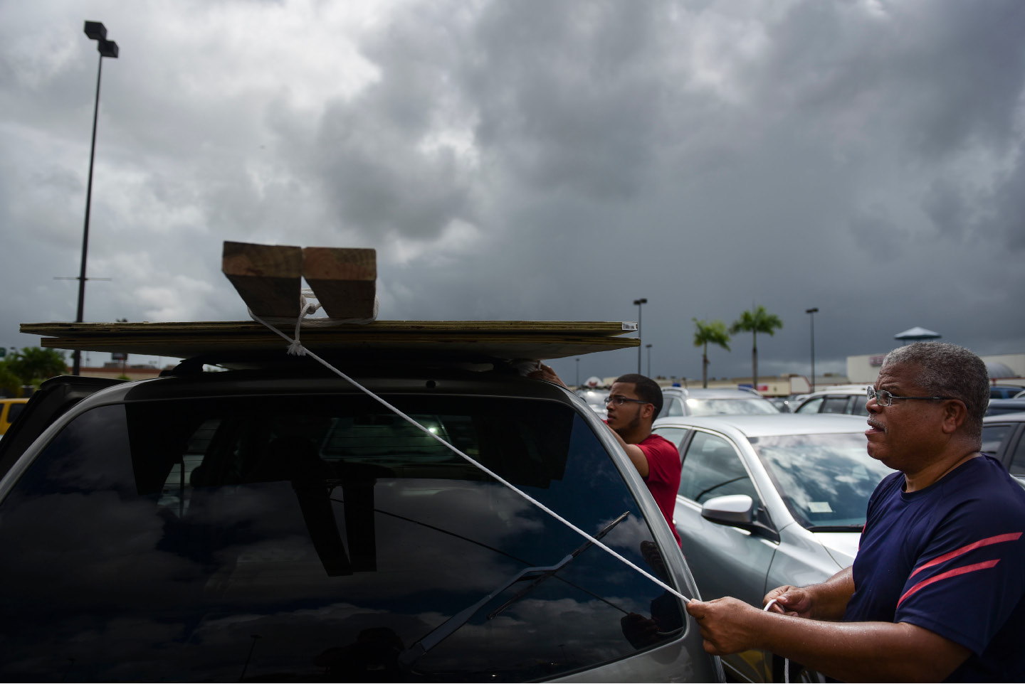 Men tie down wood panels to be used for boarding up windows in preparation for Hurricane Irma, in Carolina, Puerto Rico, Tuesday, Sept. 5, 2017. Irma grew into a dangerous Category 5 storm, the most powerful seen in the Atlantic in over a decade, and roared toward islands in the northeast Caribbean Tuesday. (AP Photo/Carlos Giusti)