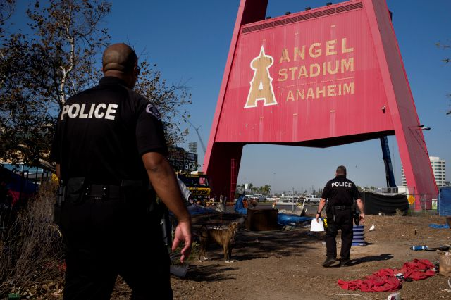 Police officers Eric Meier, right, and Curtis Bynum from the Anaheim Police Department's homeless outreach team walk through a homeless encampment set up outside Angel Stadium to hand out fliers about a community outreach day in Anaheim, Calif. The event was organized by nonprofit organizations and agencies to offer services to homeless people in Orange County. Associated Press