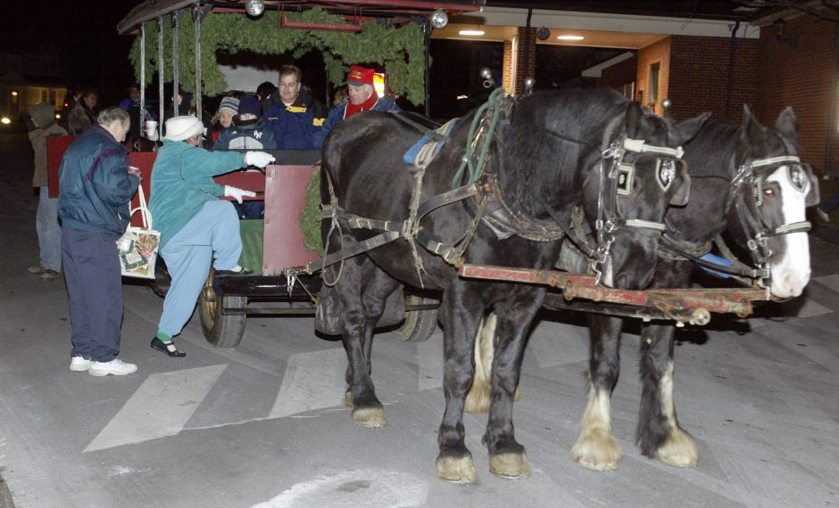 People board a horse drawn trolley Thurs. night, Dec. 4 during Christmas in the Village of Plantsville. The horses, a percheron on the left and an English shire on the right, are from Wood Acres of Terryville.