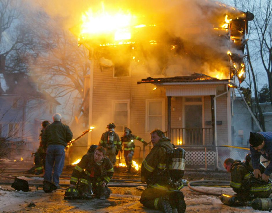 Meriden firefighters catch their breath after being ordered out of a house engulfed in flames at 16 Union Street in Meriden Monday January 16, 2006. (Dave Zajac photo)