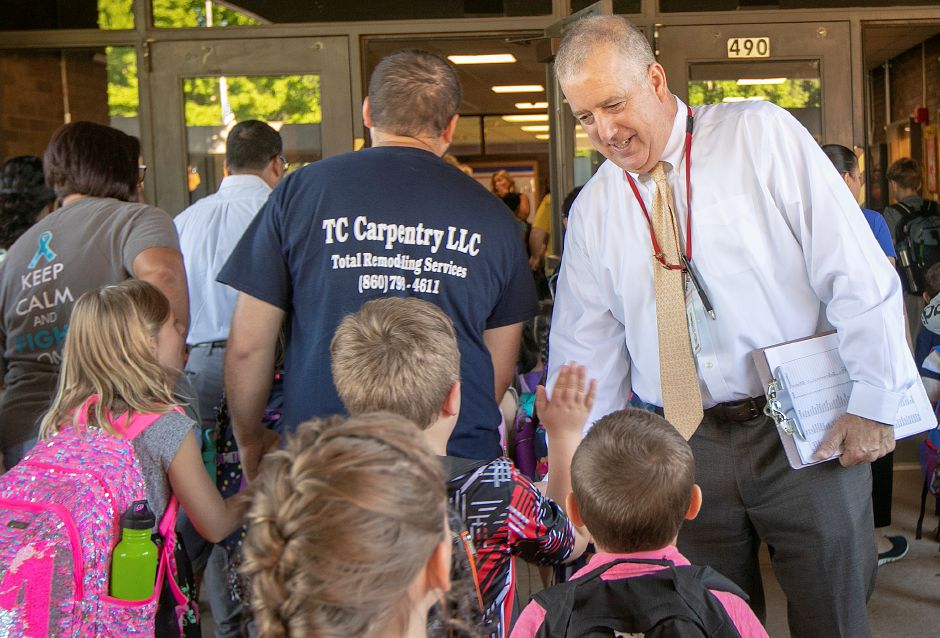 Principal Scott Jeffrey greets students on the first day of school Thursday at Highland School in Cheshire.