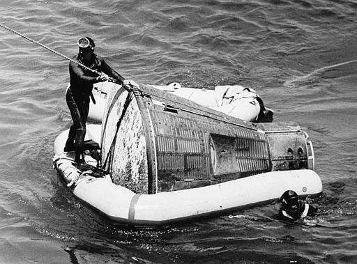 U.S. Navy divers recover the Gemini 5 spacecraft and astronauts Gordon Cooper and Charles Conrad, who orbited the earth for nearly eight days, from the Atlantic Ocean, Aug. 29, 1965. The diver at left attaches the tow line from the port side crane to the Gemini 5 space capsule prior to hoisting to the hangar bay deck of the carrier USS Lake Champlain. (AP Photo)