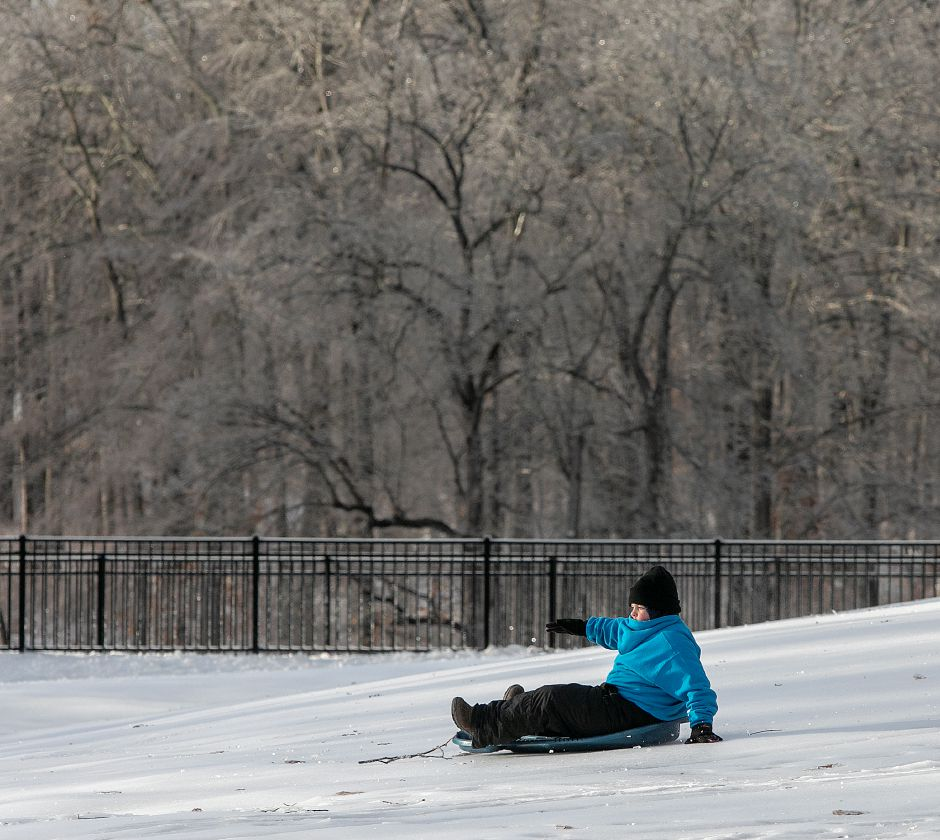 Garrett Ryder, 10, of Meriden, slides down an icy hill at Hubbard Park in Meriden.