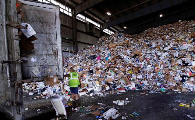 In this Thursday, Sept. 6, 2018, photo, a trailer door is opened on a truck filled with unsorted recyclable refuse as it is offloaded and added to a giant pile in a processing building at EL Harvey & Sons, a waste and recycling company, in Westborough, Mass. Recycling programs across the United States are shutting down or scaling back because of a global market crisis blamed on contamination at the curbside bin. (AP Photo/Charles Krupa)