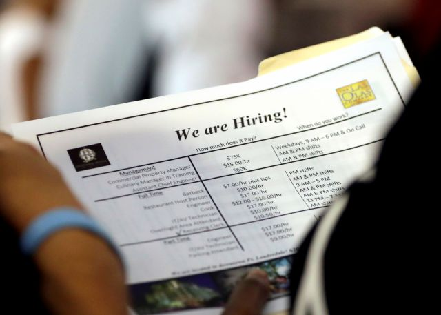 In this Thursday, June 21, 2018 photo, a job applicant looks at job listings for the Riverside Hotel at a job fair hosted by Job News South Florida, in Sunrise, Fla. (AP Photo/Lynne Sladky)
