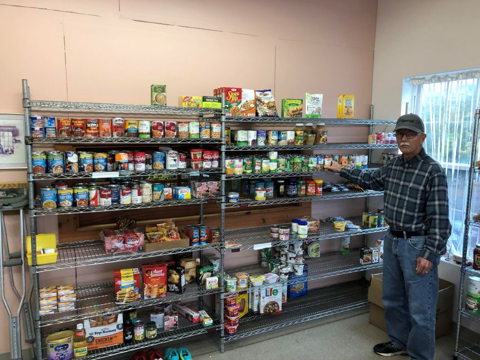 Doug Marden, a volunteer at the Durham food pantry, stands near some of the donations available for those in need. Photo courtesy of Jaclyn Lehet.