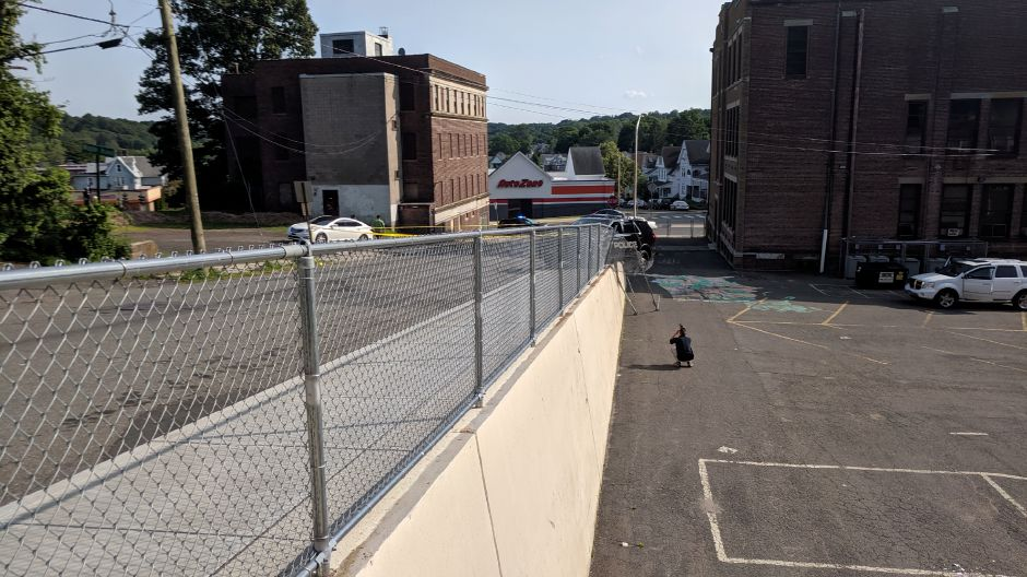 A police investigator takes photos of a police vehicle hanging over a wall on Maple Street in Meriden July 8, 2019. | Michael Gagne, Record-Journal