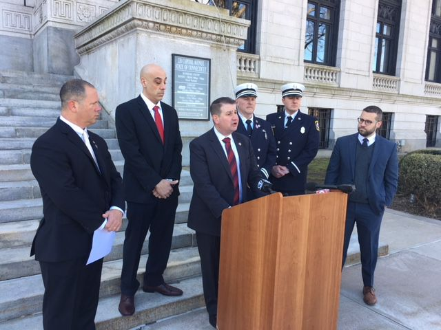 New Haven fire battalion chief Frank Ricci at the podium. Craig Fishbein, of Wallingford, is at far left; David Osborne at far right.