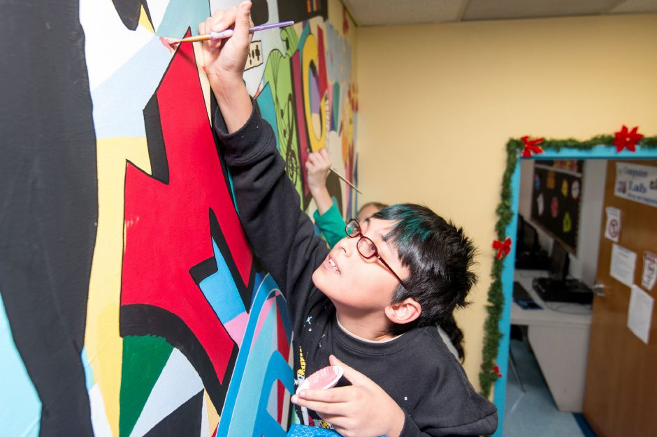 Vlad Knap, 11, paints in a bare spot in a mural being painted at the Ulbrich Boy