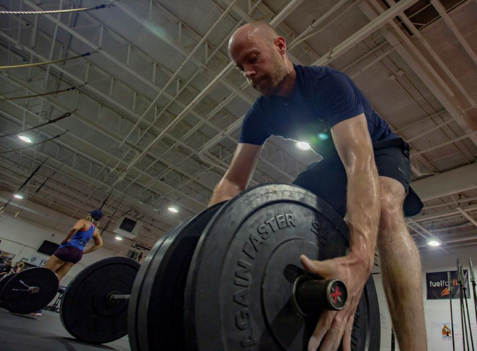 John Corkery adds weight onto a barbell during a workout at the Meriden Y Crossfit Aug. 29, 2018. | Richie Rathsack, Record-Journal