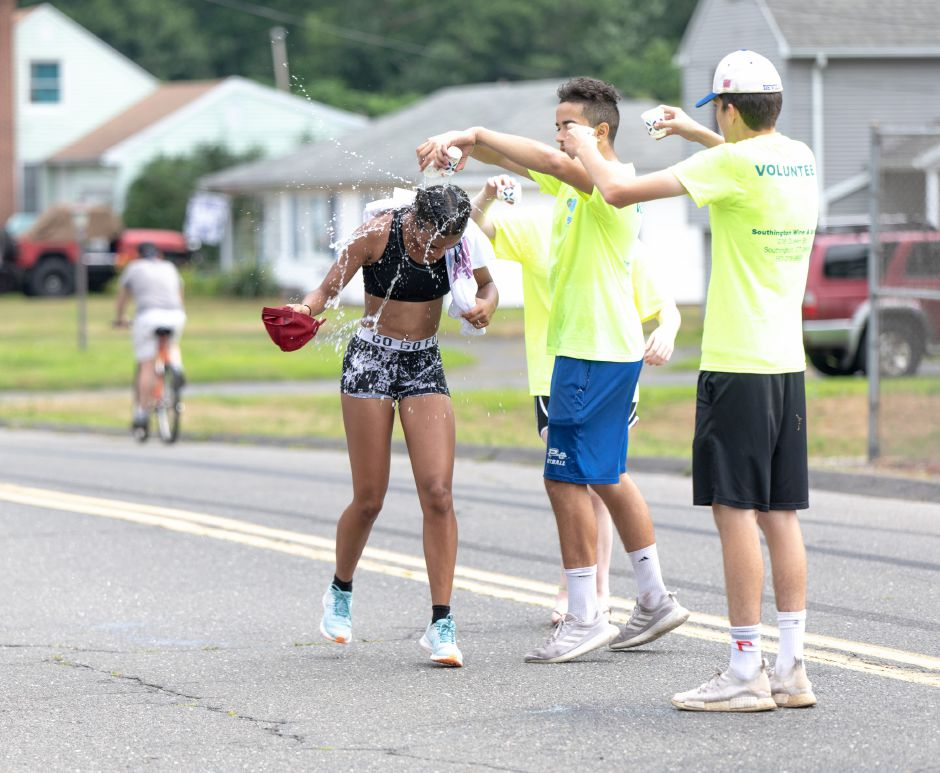 A runner in the Chips Family Restaurant Road Race gets splashed with water on July 21, 2019. Plainville residents and volunteers helped runners beat the weekend