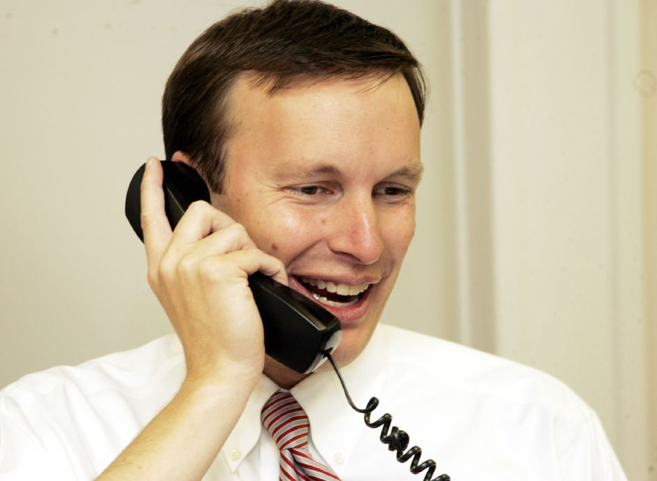 Chris Murphy is all smiles in his New Britain Headquarters Wed. morning, Nov. 8, 2006 with one of his supporters on the phone.