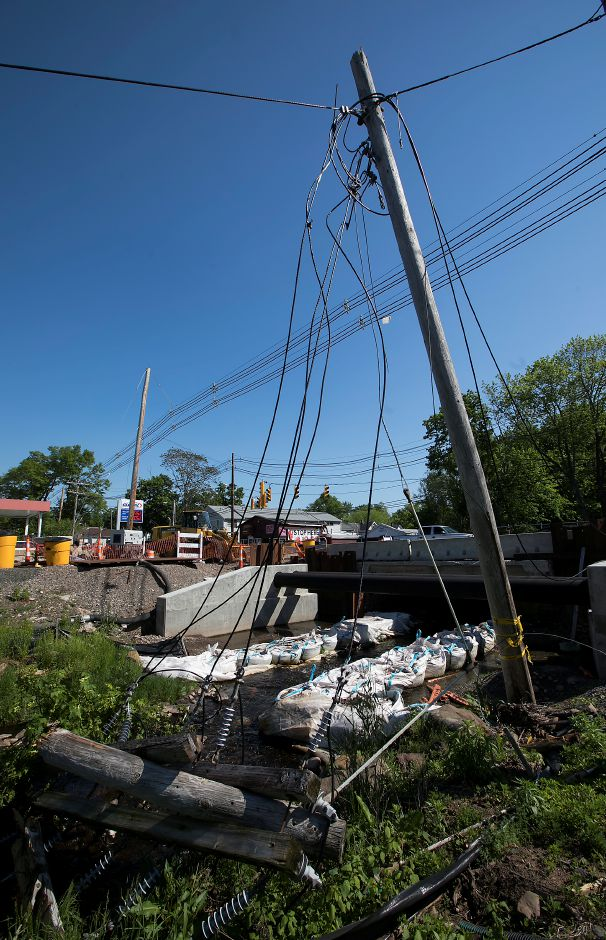 Wires down from several fallen trees near the East Center Street bridge in Wallingford, Thursday, May 24, 2018. Completion of the bridge could be delayed up to a year past the original completion date of November. Dave Zajac, Record-Journal