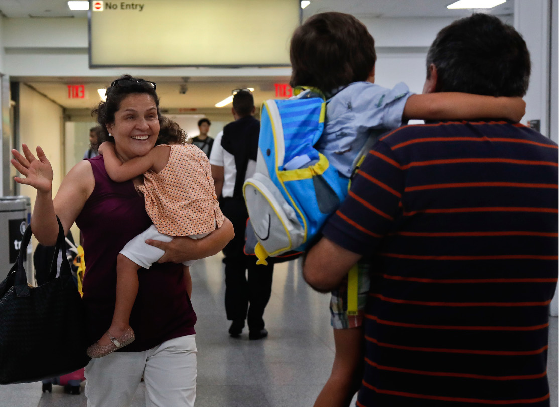 Elena Rojas, left, of Queens, N.Y. reacts as she greets her 4-year-old grandson Elias, center, while carrying her 3-year-old granddaughter Lilly after the children arrived at JFK airport from Puerto Rico with their mother Cori Rojas (not pictured), Tuesday, Sept. 26, 2017 in New York. Cori Rojas and her children fled Puerto Rico after Hurricane Maria devastated the island and will stay with her in-laws in Queens. (AP Photo/Julie Jacobson)