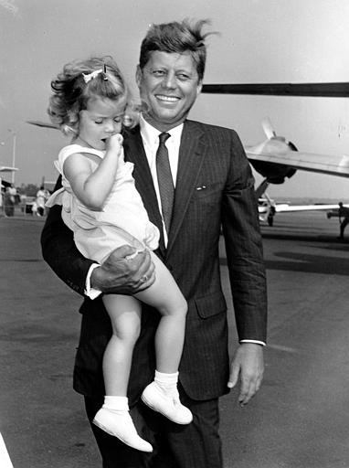Sen. John F. Kennedy, Democratic presidential nominee, carries his daughter, Caroline, 2, en route to a plane at Hyannis, Ma., on Aug. 29, 1960.  The senator, accompanied by his daughter and wife, is hurrying back to Washington, D.C., to vote on the medical care for aged bill.  (AP Photo)