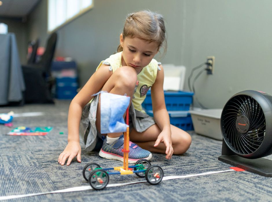 Evie Ballas, 6, of Wallingford tests a sail-powered lego car during the Wallingford School