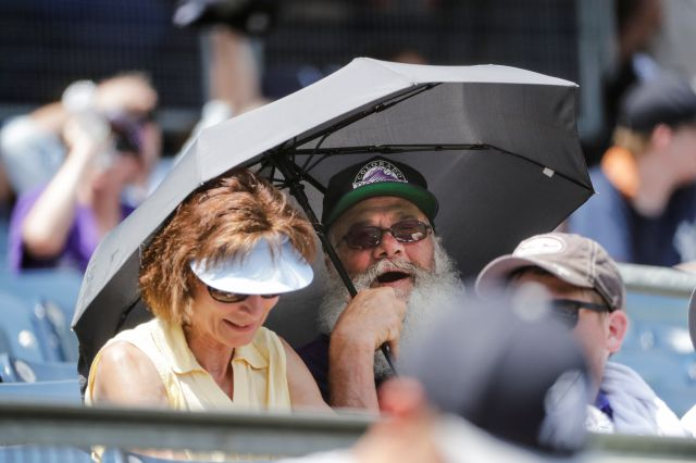 A Colorado Rockies fan uses an umbrella for shade during the third inning of a baseball game against the New York Yankees Saturday, July 20, 2019, in New York. (AP Photo/Frank Franklin II)