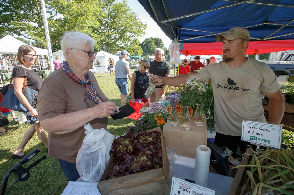 Ellie Tassmer buys a head of lettuce from Chris Wellington of Muddy Root Farm Saturday during opening weekend of the Wallingford Garden Market at Doolittle Park in Wallingford June 30, 2018 | Justin Weekes / Special to the Record-Journal