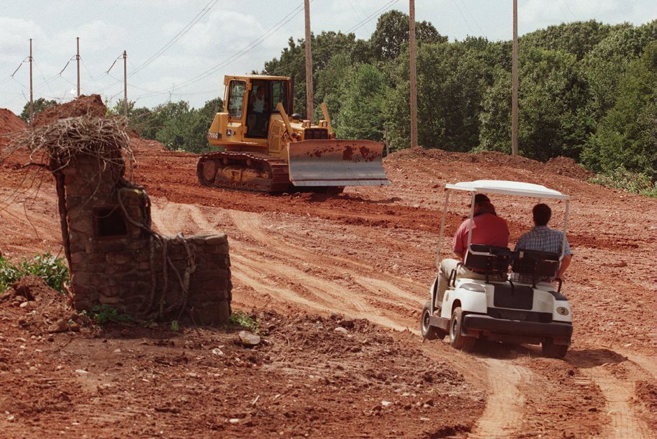 RJ file photo - Harbor Ridge Course Architect Ted Manning drive a cart near the remains of a chimney that workers found while they were clearing the 11th fairway, though there was no evidence of a foundation, Aug. 1998.