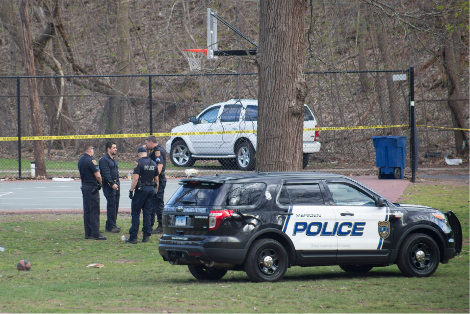 Police confer near the basketball court at City Park in Meriden while investigating a shooting Wednesday April 29, 2015. | Richie Rathsack/Record-Journal