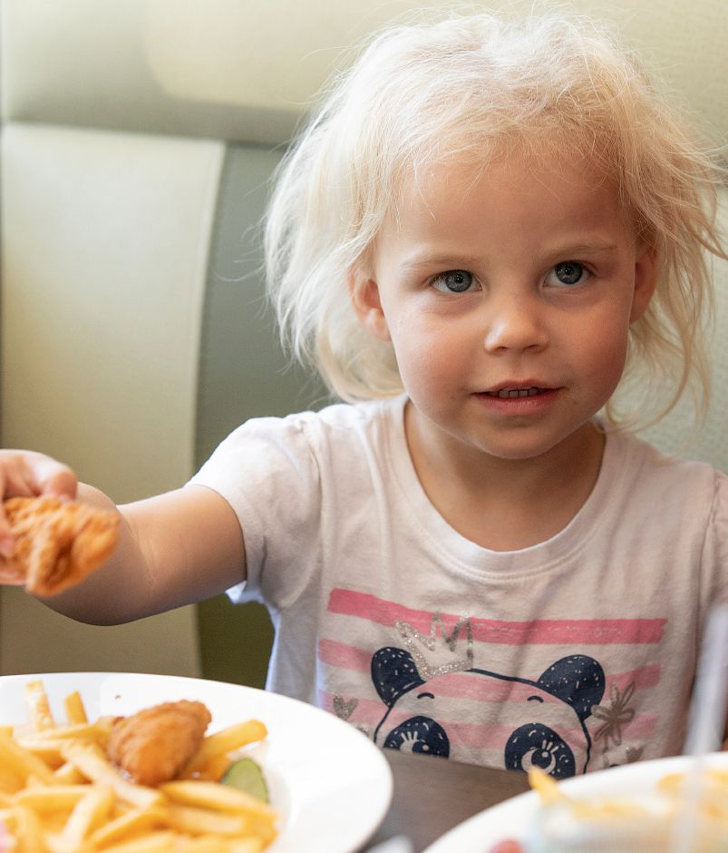 Amyalin Cruz, 2, of Meriden, enjoys chicken tenders and fries at the new Huxley