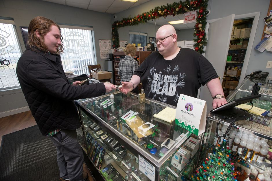 Alex May, 21, of Wallingford,  makes a purchase from Jason Thomas at Silver City Vapors in Wallingford on Wednesday.