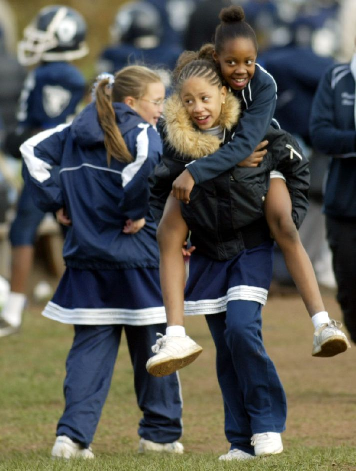 Keara Moreno, 9, of Meriden carries fellow cheerleader Zhane Wright, 9, of Meriden after the Meriden Raiders defeated the Hartford Wildcats 26-0 during a postseason game at Washington Park in Meriden Sunday afternoon October 29, 2006. (dave zajac photo)