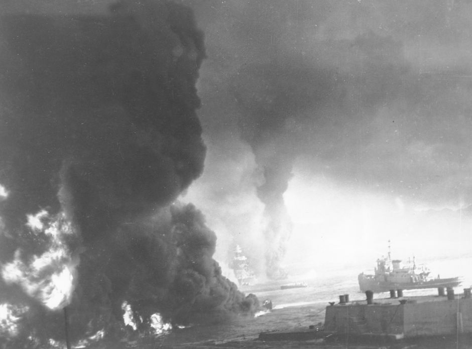 Heavy black smoke billows as oil fuel burns from shattered tanks on ships that were hit during the Japanese attack on Pearl Harbor, Hawaii on Dec. 7, 1941 during World War II. Visible through the murk is the U.S. battleship Maryland, center, and the hulk of the capsized USS Oklahoma to the right of it. (AP Photo/U.S. Navy)