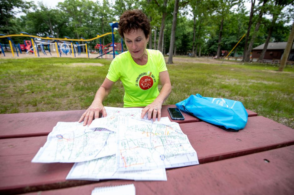 Sharon Spinelli, of Plainville, unfolds the maps where she kept track of all the streets she had run in town. Between the start of February 2018 and June 27, she ran every road in Plainville. | Devin Leith-Yessian/Plainville Citizen