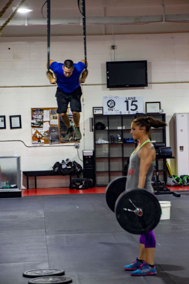 Brandon Threloff lifts himself up on the rings while Jess Valentin lifts barbells during a session at the Meriden Y Crossfit Aug. 29, 2018. | Richie Rathsack, Record-Journal