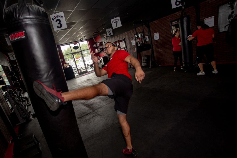Christian Pagan, an instructor at 9Round Fitness in Wallingford, demonstrates a kick on the bag at the Wallingford facility Sept. 24, 2018. | Richie Rathsack, Record-Journal