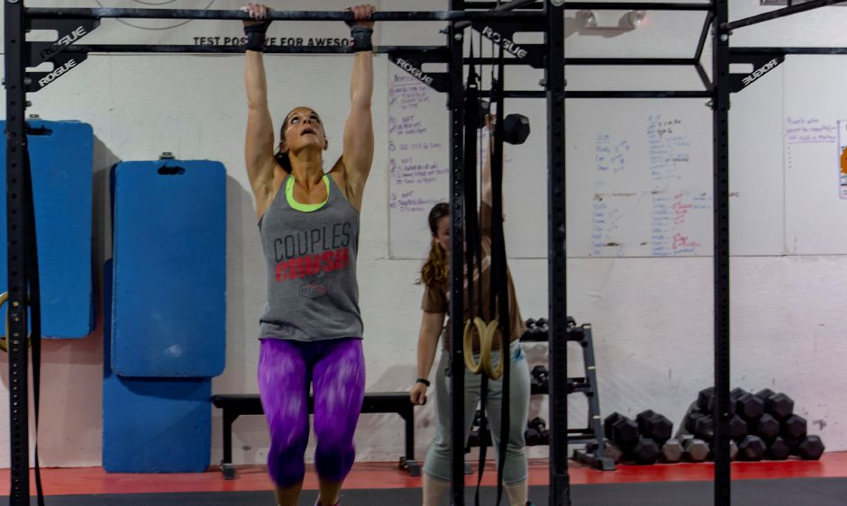 Jess Valenin, left, grabs a bar for pullups while Arielle Van Deusen lifts a dumbell at Meriden Crossfit Aug. 29, 2018. | Richie Rathsack, Record-Journal
