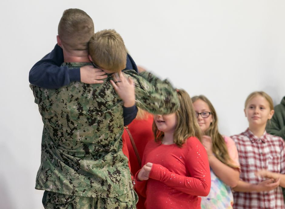 Brandon Selvaggi, U.S. Navy, of Wallingford, surprises brother, Robert Crowell, 10, and sister, Hailey Crowell, 9, during  a presentation by students and staff at Mary G. Fritz School in Wallingford on Nov. 8. Dave Zajac, Record-Journal