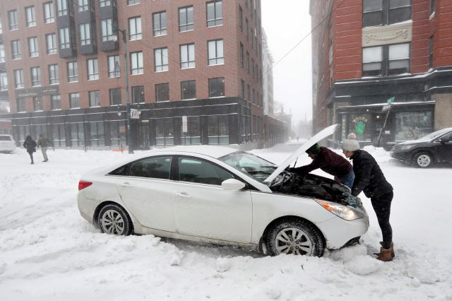 Motorists try to fix their windshield wipers during a winter storm, Sunday, Jan. 20, 2019, in Portland, Maine. Snow, sleet and freezing rain is making travel hazardous throughout much of New England. (AP Photo/Robert F. Bukaty)