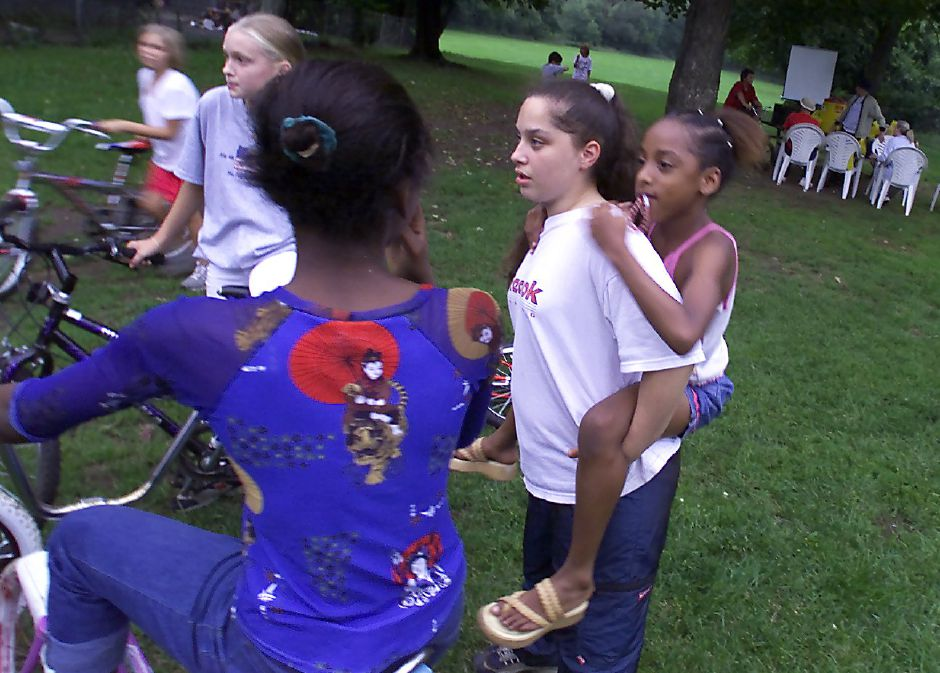 Lashae Wilds (cq),9, clings piggy back on Jessica Wright,16 while waiting for the movie to start at Bronson Park as part of National Night Out on Tuesday. Next to them (from left to right) are Brittany Krol,9 ( blurry girl on far left), her sister Kristina Krol (cq) and Tiesha Rollins,12 (seated on bike with her back to the camera).
