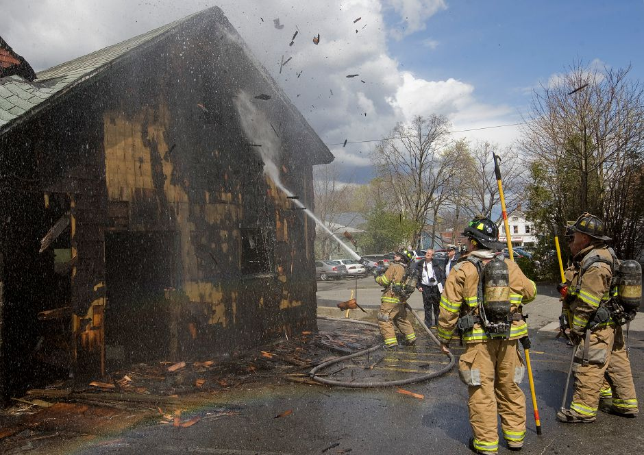 Meriden firefighters blast water on a building at 34 High Street behind First Baptist Church after a fire was reported there Thursday April 12, 2012. No injuries were reported in the blaze which broke out around noon. (Dave Zajac/Record-Journal)