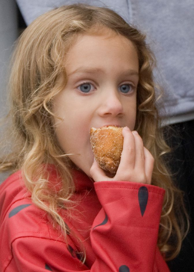 Ella Reed, 4, of Southington, bites into an apple fritter on opening night of the 48th Annual Apple Harvest Festival in Southington, Friday, September 30, 2016. The festival runs September 30, October 1-2 & October 7-9. | Dave Zajac, Record-Journal