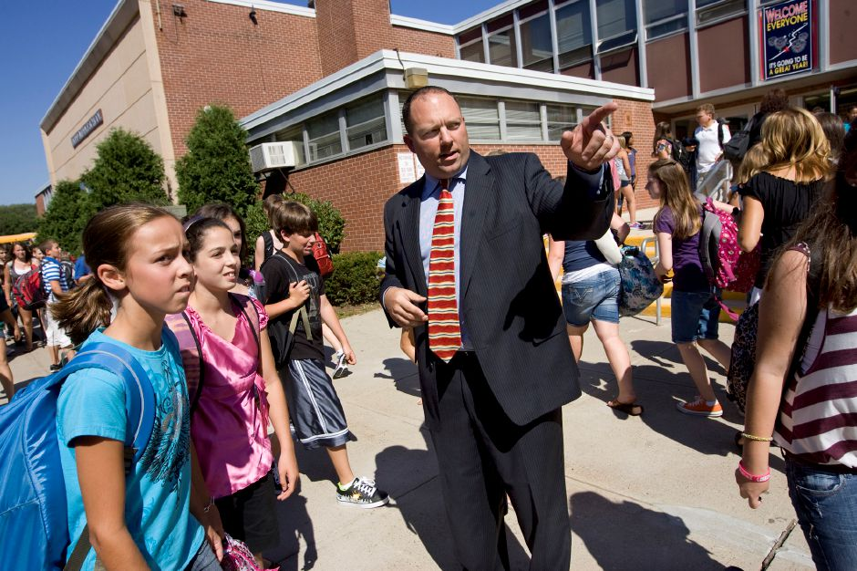 FILE PHOTO: Then Principal Jeffrey Solan helps 7th grade students Allyson Braun, 12, far left, and Marissa Jamele, 12, find their buses after completion of the first day of school at Dodd Middle School in Cheshire August 30, 2010. (Dave Zajac/Record-Journal)