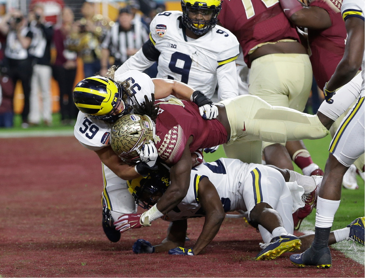 Florida State running back Dalvin Cook (4) scores a touchdown as Michigan linebacker Noah Furbush (59) defends, during the first half of the Orange Bowl NCAA college football game, Friday, Dec. 30, 2016, in Miami Gardens, Fla. Below Cook is Michigan cornerback Brandon Watson (28). (AP Photo/Alan Diaz)