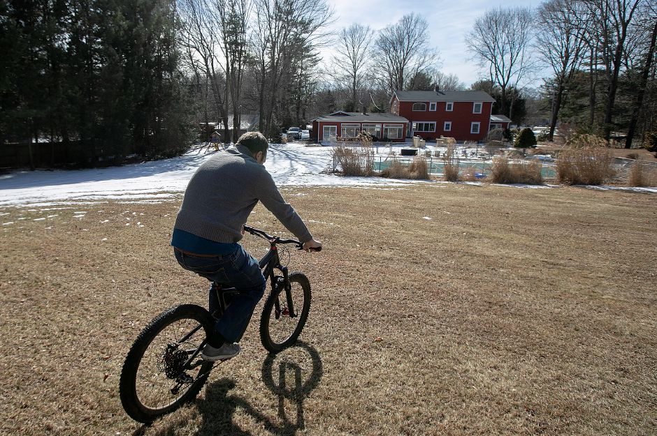Ken Roe, of Wallingford, rides his mountain bike in the backyard of his residence on Pine River Road which abuts the closed Tyler Mill Preserve in Wallingford, Tues., Feb. 19, 2019. Dave Zajac, Record-Journal