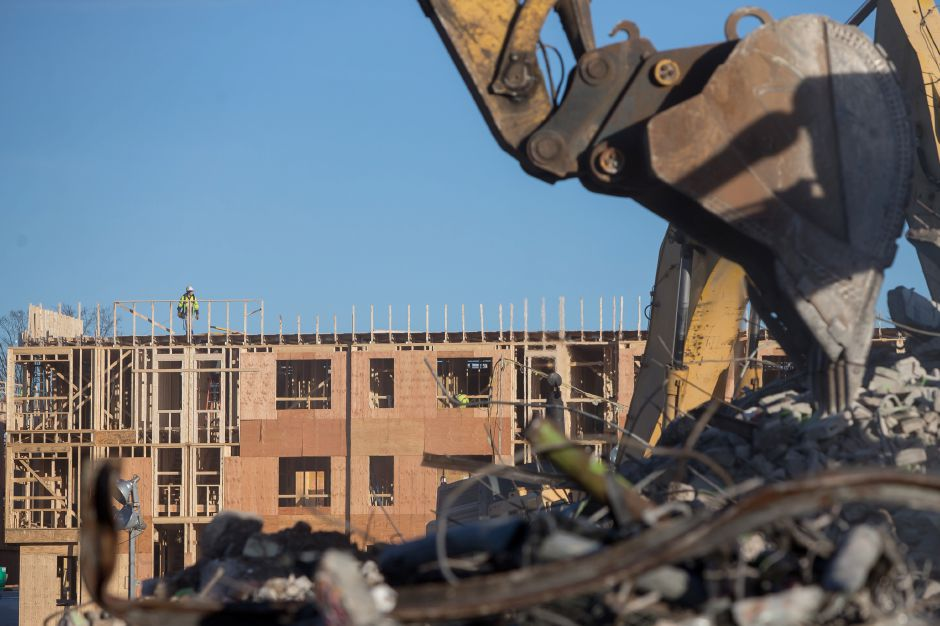 A construction worker stands atop the new construction watching demolition crews take down the last Mills Apartment building Thursday in Meriden December 27, 2018 | Justin Weekes / Special to the Record-Journal