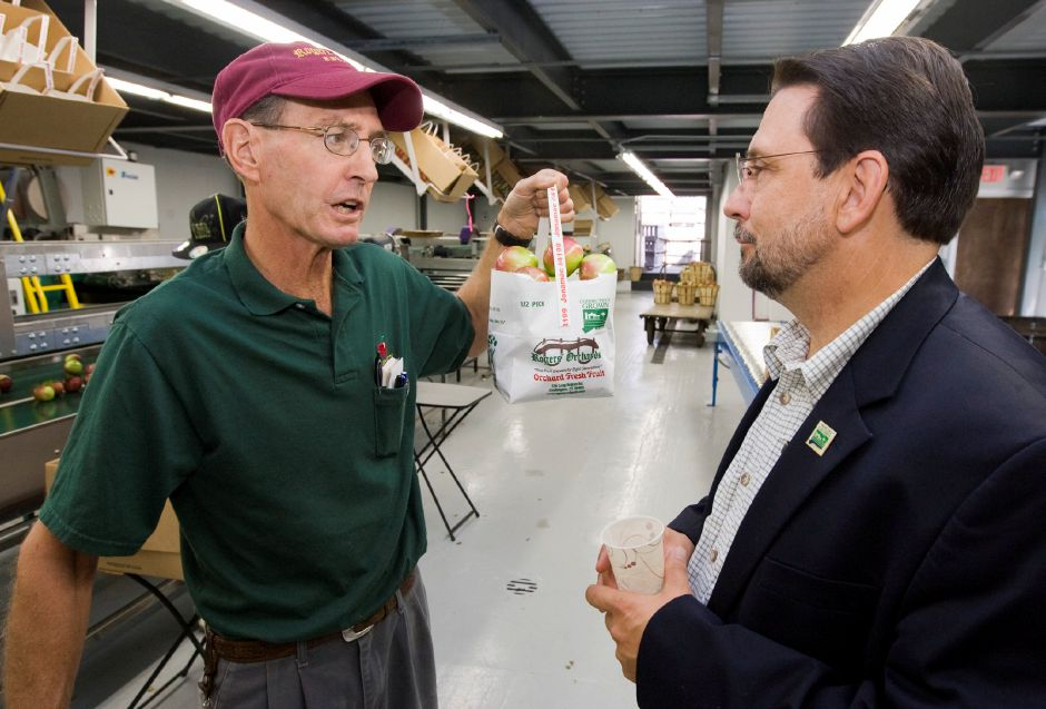 Rogers Orchards is TripAdvisor.com's No. 1 thing to do in Southington. In this file photo, John Rogers shows Commissioner of Agriculture Steven Reviczky a one-half peck tote Sept. 2, 2011. (Christopher Zajac / Record-Journal)