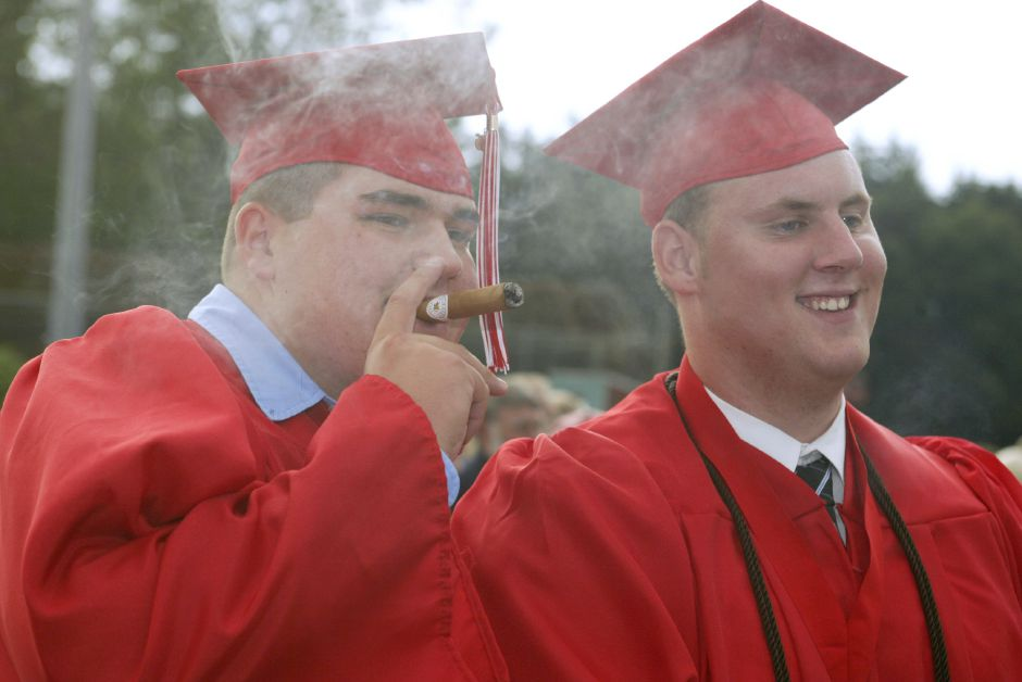 Tim Maffuid, 18, left, and Brian Wycinowski, 18, celebrate their graduation from Cheshire H.S. with a cigar after the ceremony on June 20, 2006